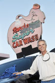 Portrait of mature owner of car wash standing below signboard with vehicle — Stock Photo