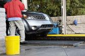 Auto-waschanlagen-mitarbeiter mit fahrzeug auf förderband — Stockfoto