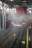Vehicle on conveyor belt moving through car wash process — Stock Photo