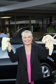 Portrait of cheerful female owner showing washcloth in car wash — Stock Photo