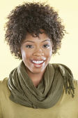 Portrait of an African American woman with a stole round her neck smiling over colored background — Stock Photo