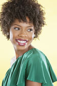 Attractive African American woman in an off shoulder dress looking away over colored background — Stock Photo