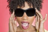 Nahaufnahme einer afroamerikanischen frau mit sonnenbrille auf farbigen hintergrund — Stockfoto