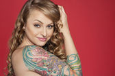 Portrait of beautiful young tattooed woman over colored background — Stock Photo