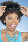 Cheerful African American woman adjusting sunglasses over colored background — Stock Photo