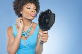 Attractive African American woman puckering while looking in mirror over colored background — Stock Photo