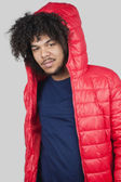 Portrait of young man wearing red jacket with hood over colored background — Stock Photo