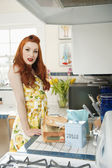 Portrait of a redheaded woman standing by the kitchen counter — Stock Photo