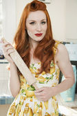 Portrait of a confident redheaded woman holding a rolling pin — Stock Photo