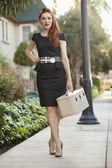 Toute la longueur d'une femme élégante dans une robe à pied avec un cas de vanité — Photo