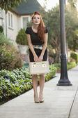完整长度的一个时尚的女人抱着化妆盒 — 图库照片