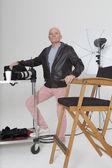 Celovečerní portrét starší fotografa s zařízení ve studiu — Stock fotografie