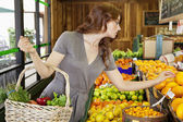 Beautiful young female shopping for fruits in market — Stock Photo