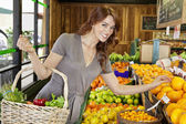 Portrait of a happy young female shopping for fruits in market — Stock Photo