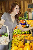Happy young woman shopping in supermarket for fruits — Stock Photo