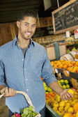 Portrait of handsome young man shopping for fruits in market — Stock Photo