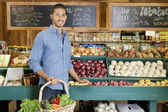 Handsome young man holding basket at vegetable stall in supermarket — Stock Photo