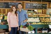 Portrét šťastný mladý pár v zeleninovém trhu — Stock fotografie