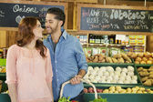 Happy young couple shopping together for vegetables in market — Stock Photo