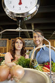 Happy young couple looking at weight scale in supermarket — Stock Photo