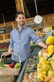 Bel giovane uomo shopping per frutti nel supermercato — Foto Stock
