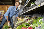Happy young man shopping for vegetables in market — Stock Photo