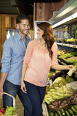 Happy young couple looking at each other while shopping for vegetables in market — Stock Photo
