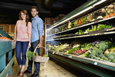 Portrait of young couple standing with vegetable basket in supermarket — Stock Photo