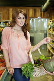 Portrait of beautiful young woman with basket in supermarket — Foto de Stock