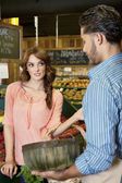 Woman looking at store clerk in supermarket — Stockfoto