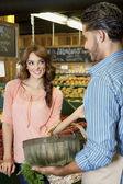 快乐的年轻女人看着超市店员 — 图库照片
