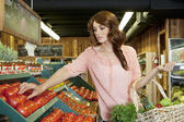 Beautiful brunette woman shopping for tomatoes in supermarket — Stock Photo