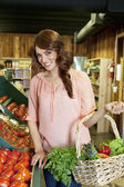 Portrait of beautiful brunette holding basket near tomato stall in market — Stock Photo