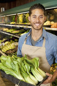 Portrait of handsome young sales clerk with bok choy in market — Stock Photo