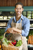 Portrait of handsome young salesperson standing with basket full of vegetables — Stock Photo