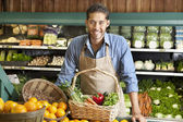 Portrait of a happy young salesman with vegetable basket in supermarket — Stock Photo