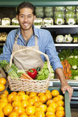 Portrait of a happy man with vegetable basket standing near oranges stall in supermarket — Foto Stock