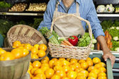 Midsection of man standing near oranges stall with vegetable basket in supermarket — Stock Photo