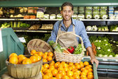 Portrait of man in supermarket with vegetable basket standing near oranges stall — Foto Stock