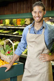Handsome young sales clerk standing near stall in supermarket — Stock Photo