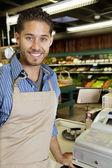 Portrait of handsome store employee standing near cash register in supermarket — Stock Photo