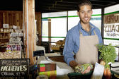Portrait of handsome young store clerk holding vegetable in supermarket — Stock Photo