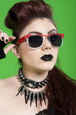 Close-up of young punk woman wearing sunglasses over green background — Stock Photo