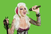 Beautiful tattooed woman singing with microphone over green background — Stock Photo