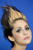 Close-up portrait of beautiful young woman with spiked hair over blue background — Stock Photo
