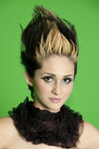 Portrait of beautiful young woman wearing scarf with spiked hair over green background — Stock Photo