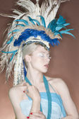 Beautiful young woman wearing feather headgear with eyes closed — Stock Photo
