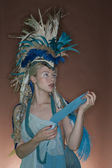 Beautiful young woman wearing costume with feather headgear over colored background — Stock Photo