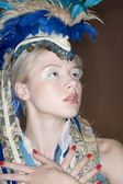 Close-up of beautiful young woman with feathered headdress — Stock Photo