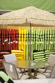 Parasol met tafel en stoel in winkel — Stockfoto